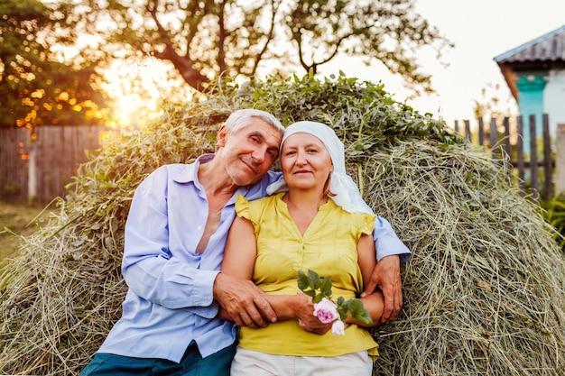 Familiepaar van landbouwers die op hooiberg zitten en bij zonsondergang in platteland ontspannen.