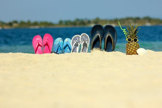 Familiepantoffels op het zand op het strand in de zomer