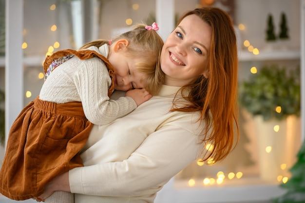 Familieportret, gelukkige moeder en dochter in de kersttijd