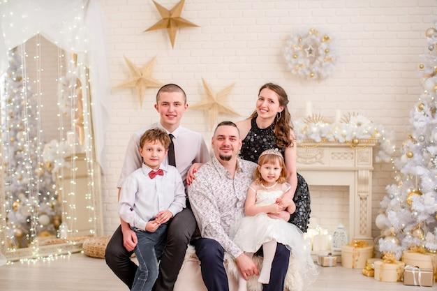Familieportret in de studio ingericht voor het nieuwe jaar. kerst familieavond. familie om samen te komen knuffelen en glimlachen. ingerichte woonkamer met open haard en kerstboom