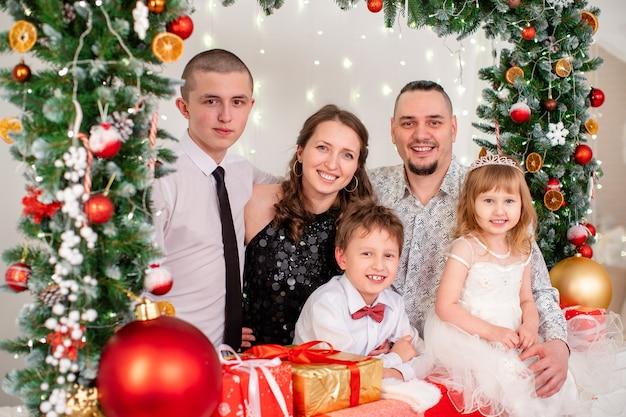 Familieportret in de studio ingericht voor het nieuwe jaar. kerst familieavond. familie om samen te komen knuffelen en glimlachen. naaldslinger versierd met kerstspeelgoed.
