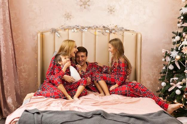 Familieportret in pyjama liggend op bed. moeder, vader en twee kinderen hebben plezier in de slaapkamer. kerstmis en nieuwjaar concept