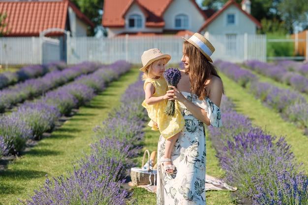 Familieportret op lavendelgebied, moeder en dochter die samen pret hebben