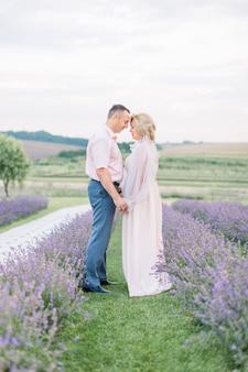 Familieportret van een knappe man van middelbare leeftijd en een mooie vrouw, die buiten op het lavendelveld staat, handen vasthoudt en voorhoofden aanraakt. huwelijksverjaardag concept. liefde door de jaren heen