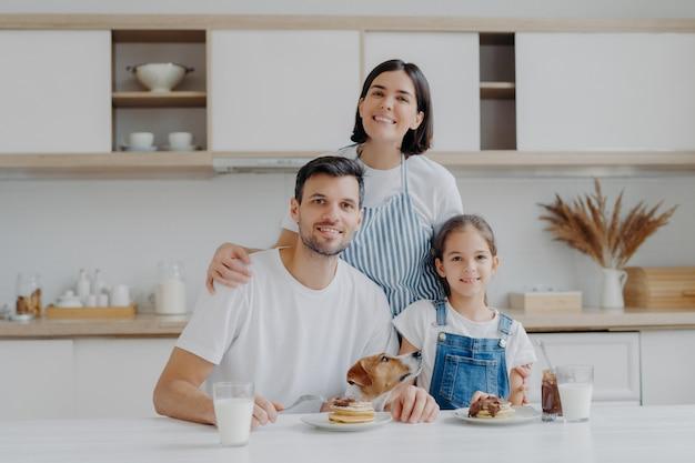 Familieportret van gelukkige moeder, dochter en vader poseren in de keuken tijdens het ontbijt, eten heerlijke zelfgemaakte pannenkoeken, hun hond poseert dichtbij, hebben vriendelijke goede relaties, houden van elkaar