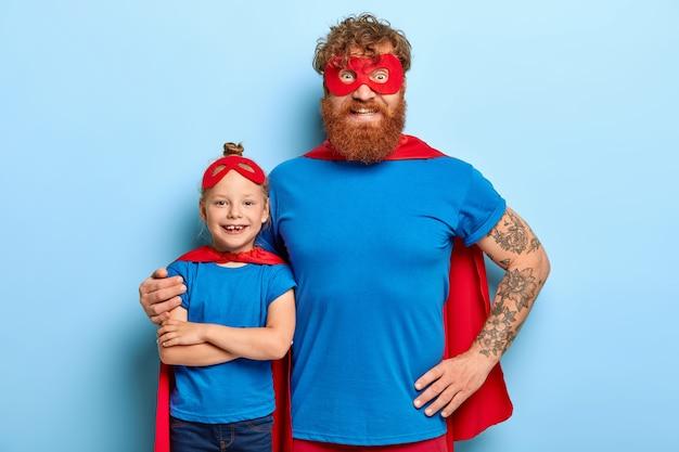Familieportret van grappige vader en dochter spelen superheld