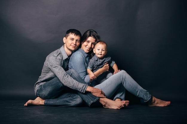 Familieportret van ouders en kind in casual stijl denim kleding. mode-modellen camera kijken op grijze achtergrond.