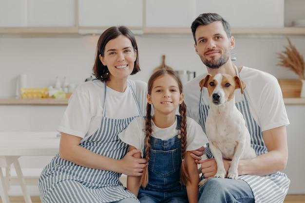 Familieportret van vader, moeder, dochter en rashond poseren samen