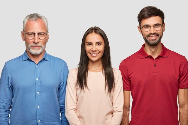 Familieportret van volwassen grijze man en zijn aantrekkelijke zoon, dochter, staan dicht bij elkaar, poseren voor albumfoto's, hebben vrolijke uitdrukkingen, hebben goede relaties. mensen, leeftijd en familieconcept