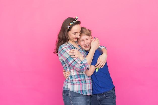 Familieportret zus en tiener broer op roze achtergrond