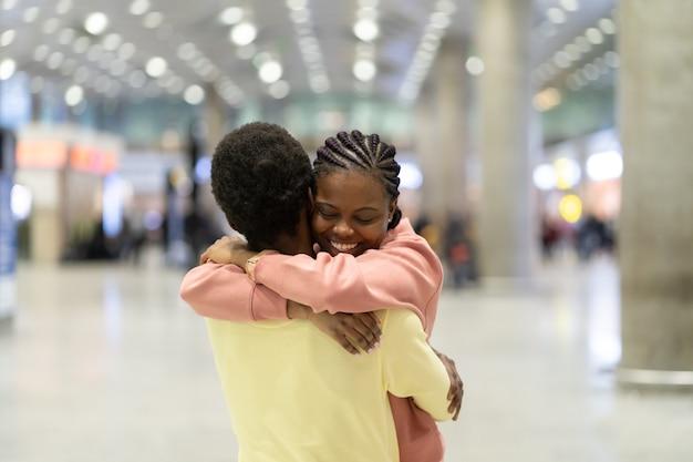 Familiereünie in luchthaven gelukkige zwarte man knuffelen opgewonden vrouw na aankomst vliegtuig in terminal
