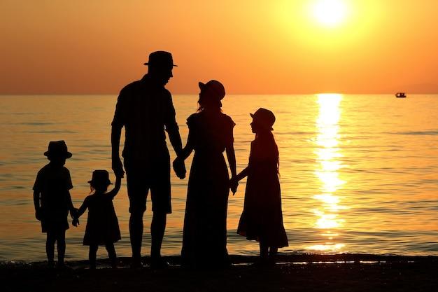 Familiesilhouet bij zonsondergang aan zee in de zomer