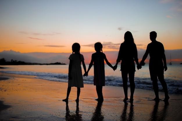 Familiesilhouet in de zonsondergang bij het strand