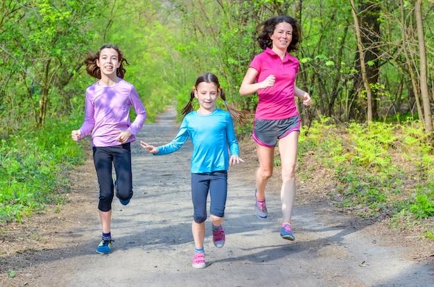 Familiesport en fitness, gelukkige actieve moeder en jonge geitjes die in openlucht aanstoten, die in bos, het gezonde concept van de levensstijlfamilie lopen