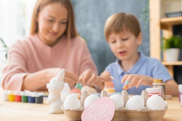 Familietraditie voor pasen: focus op eieren in karton en roze paaskaart, moeder en zoon die eieren schilderen