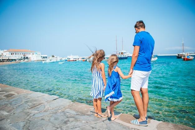 Familievakantie in europa. vader en kinderen achtergrond mykonos-stad in griekenland