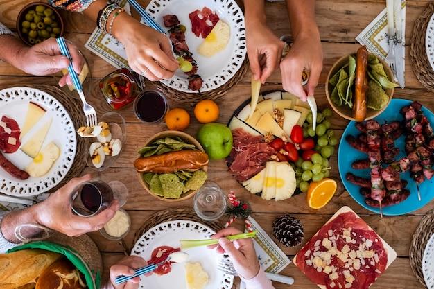 Familievrienden hebben samen plezier in de winter en eten op een houten tafel