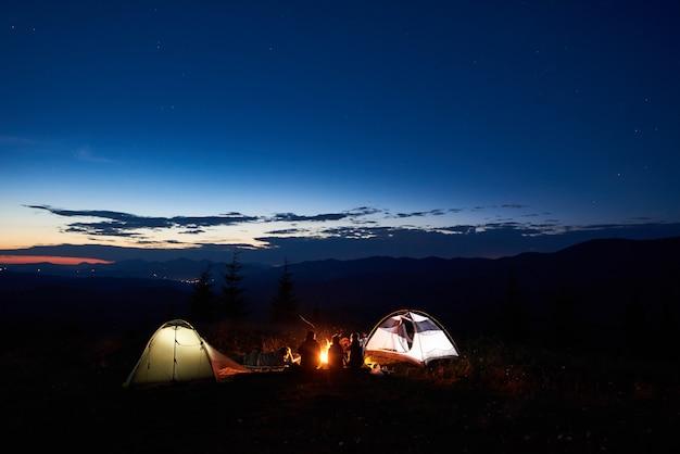 Familiewandelaars die een rust hebben bij nacht die in bergen kamperen