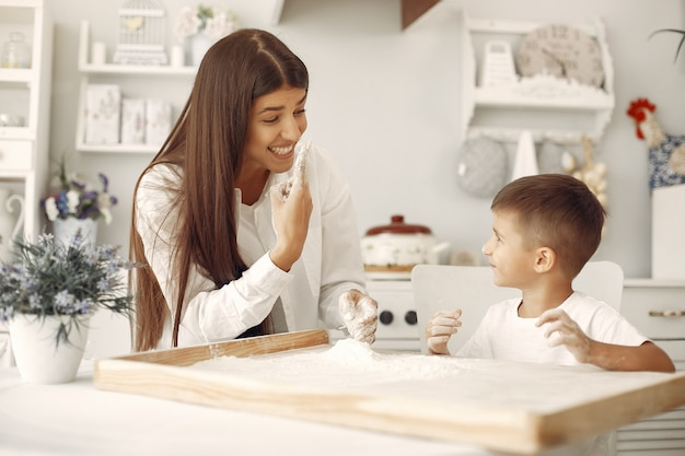 Familiezitting in een keuken en kook het deeg voor koekjes