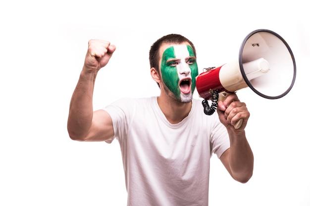 Fan ondersteuning van nigeria nationale ploeg met geschilderde gezicht schreeuwen met luidspreker geïsoleerd op een witte achtergrond