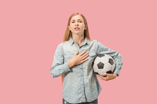Fan sport vrouw speler met voetbal geïsoleerd op roze studio achtergrond