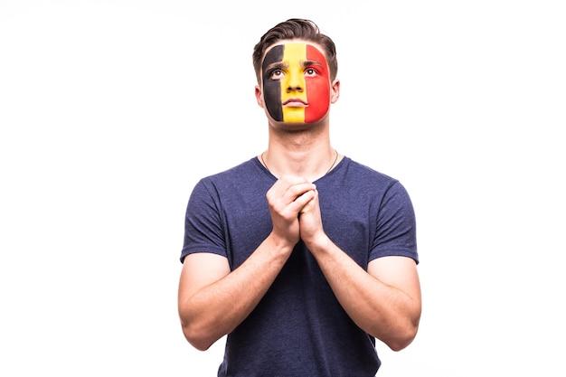 Fan steun van het belgische nationale team bidt met geschilderd gezicht geïsoleerd op een witte achtergrond