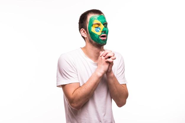 Fan-steun van het braziliaanse nationale team bidt met geschilderd gezicht geïsoleerd op een witte achtergrond