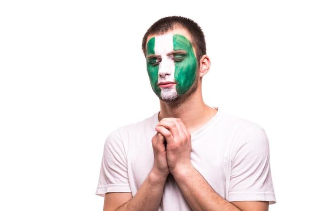 Fan-steun van het nationale team van nigeria bidt met geschilderd gezicht geïsoleerd op een witte achtergrond