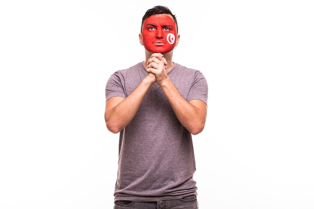Fan-steun van het nationale team van tunesië bidt met geschilderd gezicht geïsoleerd op een witte achtergrond