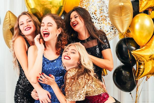 Fancy cocktailparty. meisjes genieten van entertainment, lachen, plezier maken, geamuseerd kijken in de hal versierd met gouden ballonnen.
