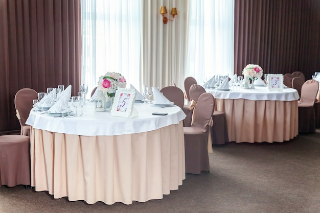 Fancy tafel set voor het diner met bloem samenstelling in restaurant, luxe interieur achtergrond. bruiloft elegante banket decoratie en items voor eten geregeld door cateringservice op witte tafel.