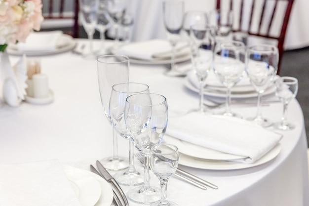 Fancy tafel set voor het diner met servetglazen in restaurant, luxe interieur achtergrond. bruiloft elegante banket decoratie en items voor eten geregeld door cateringservice op witte tafelkleed tafel.