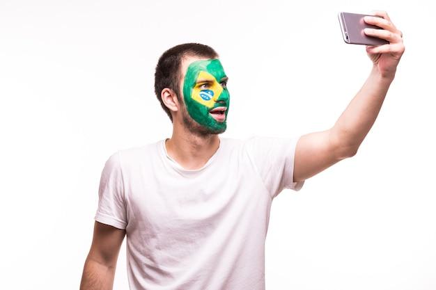 Fanondersteuning van het braziliaanse nationale team neemt selfie aan de telefoon met geverfd gezicht geïsoleerd op een witte achtergrond