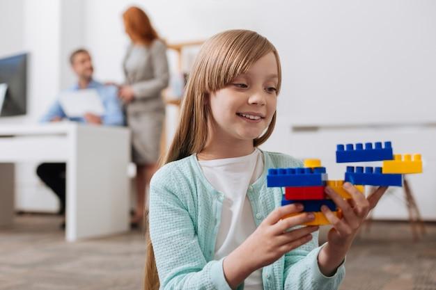 Fantasierijk vrolijk betoverend meisje speelt met bouwdoos