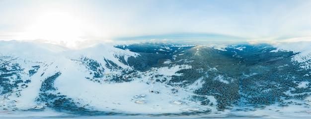 Fantastisch avondpanorama met met sneeuw bedekte bergen en heuvels met felle zon en mist op een ijzige winteravond. mooi hard noordelijk natuurconcept. copyspace