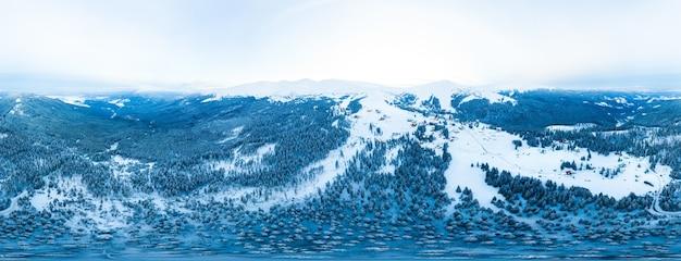 Fantastisch besneeuwd panorama van sparren die op de berghellingen groeien in de winter bij bewolkt, mistig weer