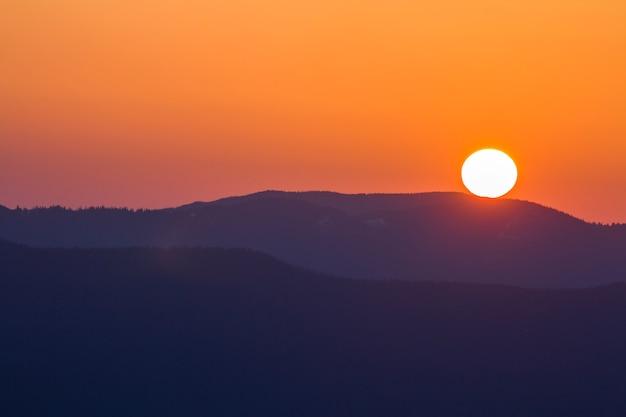 Fantastisch breed panorama uitzicht op grote heldere witte zon in dramatische oranje hemel over donkere paarse bergketen bij zonsondergang of zonsopgang in de karpaten. schoonheid en pracht van de natuur concept.