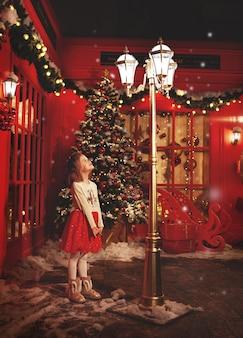 Fantastisch klein meisje dat met kerstmis op winterstraat staat en naar licht kijkt kind in de buurt van rode winkel