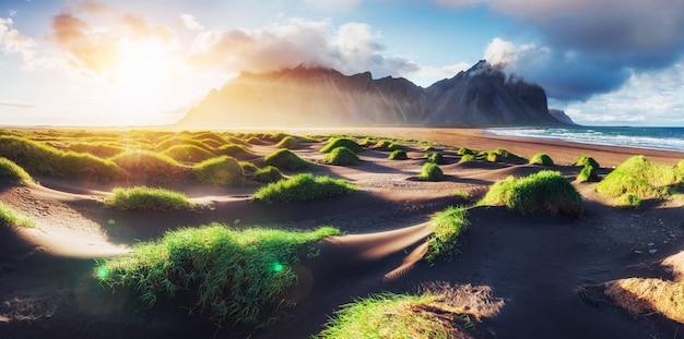Fantastisch ten westen van de bergen en vulkanische lavazandduinen op het strand stokksness