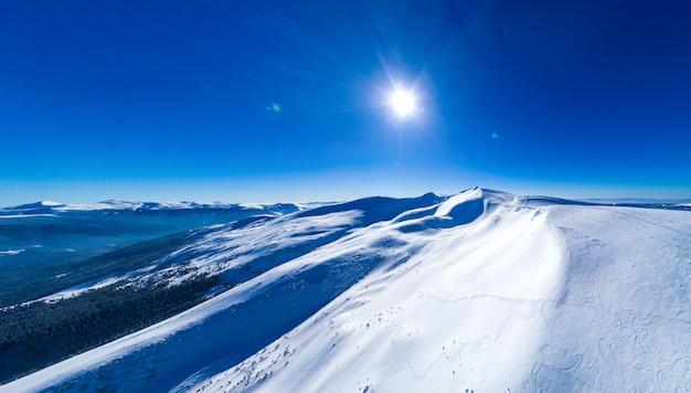 Fantastisch uitzicht op de zonnige winterhelling met besneeuwde bomen in het skigebied