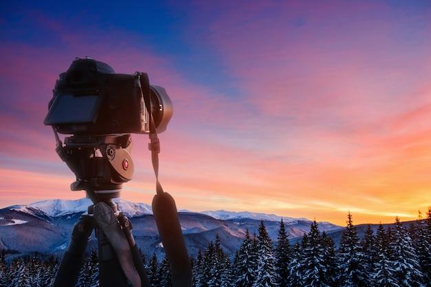 Fantastisch winterlandschap en versleten pad dat leidt naar de bergen. zonsondergang. in afwachting van de vakantie.