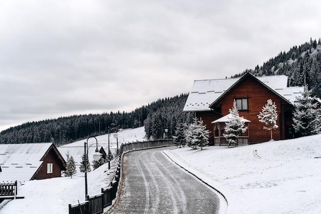 Fantastisch winterlandschap met houten huis in besneeuwde bergen. kerst vakantie concept. eenzame weg bij het dorp