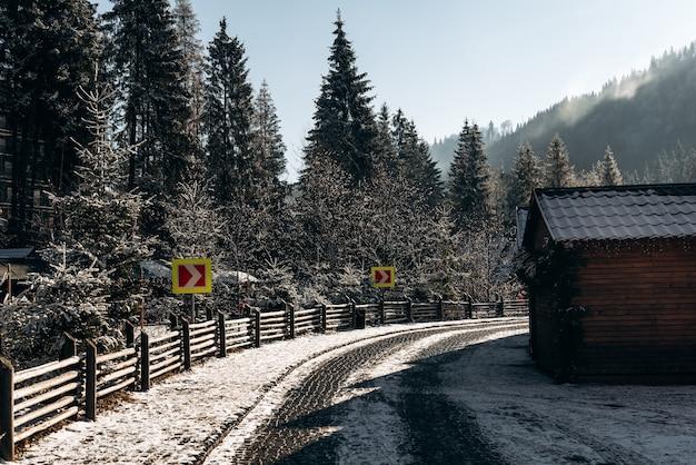 Fantastisch winterlandschap met houten huis in besneeuwde bergen. kerst vakantie concept. zonnige weg met wijzers in de buurt van het dorp