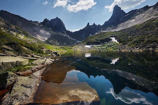 Fantastische bergen en meren, reizen en wandelen, weelderig groen en bloemen rondom. ontdooid bronwater uit de bergen. magisch uitzicht op hoge bergen, alpenweiden
