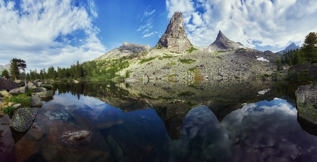 Fantastische bergen en meren, reizen en wandelen, weelderig groen en bloemen rondom. ontdooide bronwater uit de bergen. magisch uitzicht op hoge bergen, alpenweiden