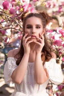 Fantastische brunette vrouw poseren in de buurt van de bloeiende magnoliaboom in modieuze jurk