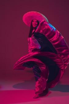 Fantastische cinco de mayo danseres op paarse muur in neonlicht.