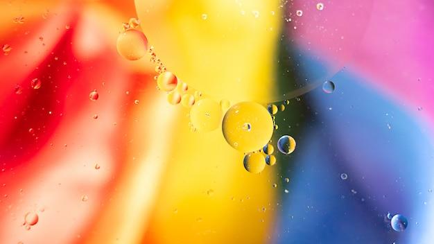 Fantastische fotostructuur van kleurrijke oliebellen. chaotische beweging. abstracte verf. plat liggen. beweging van bellen in de vloeistof. waterspiegel veelkleurige achtergrond. macro patroon. rainbow, lgbt.