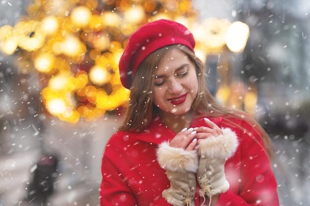 Fantastische jonge vrouw in rode jas die tijdens de sneeuwval op de straatmarkt loopt. lege ruimte