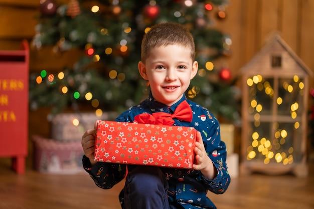 Fantastische kerst, kleine jongen met een grote rode doos met een cadeautje van de kerstman